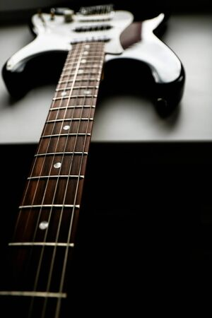 Close-up view of old bass guitar on dark background with copy space. Vertical low key photo. Banque d'images - 129037362