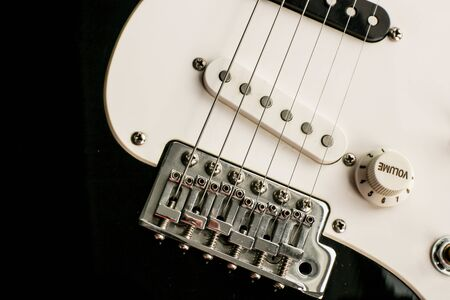 Black and white electronic guitar close up view. Details of rock guitar. Strings and volume control. Guitar as a symbol of yin yang. Banque d'images - 129037361