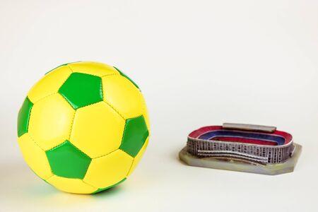 Pallone da calcio e modello dello stadio isolato su priorità bassa bianca.