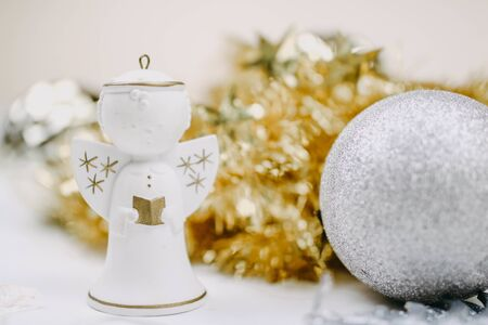 Christmas angel playing a flute with golden decoration at the background Reklamní fotografie