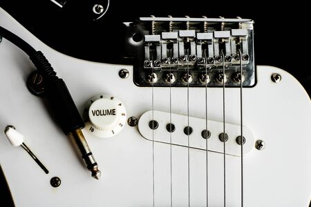 Details and connection of guitar and wire cable jack. Tone and volume controls. Close up black and white electronic guitar. Banque d'images - 129038027