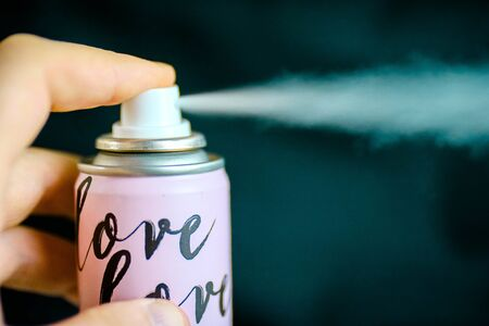 The hand is holding colorful spray bottle with deodorant and black background. Dry deodorant spray.