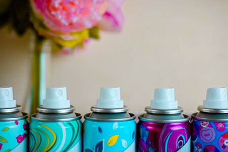 Five spray nozzles in a colorful metal cylindres. Close up. Blurred background.