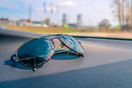 Elegant fashionable plastic men's sunglasses on interior car dashboard.