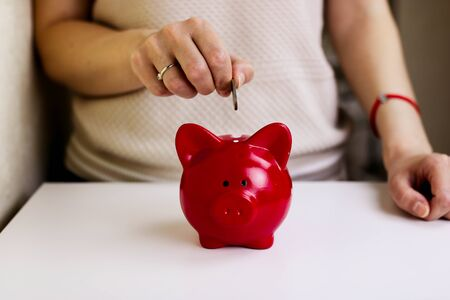 Woman inserting coins in the piggy bank at her office selective focus on the coin