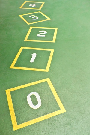 school playground: Yellow Hopscotch on Green Playground Stock Photo