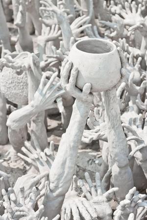Evil hands sculpture asking for donation