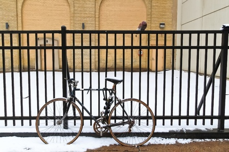 Black bicycle leaning against black iron fence in winter