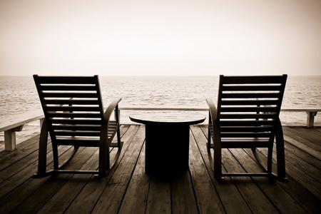 prendre sa retraite: Photo de cru de deux fauteuils � bascule en bois sur le porche en bois donnant sur l'oc�an Banque d'images
