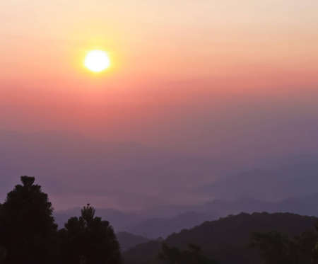 Sunrise over morning mist and layers of tropical mountain at Huai Nam Dang National Park, Mae Hong Son, Thailand photo