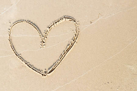 Freehand drawing of heart on sand with wave lines photo