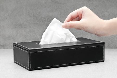 tejido: Primer plano de una mano de la mujer tirando de un pa�uelo de papel a partir de un tejido de recuadro negro Foto de archivo