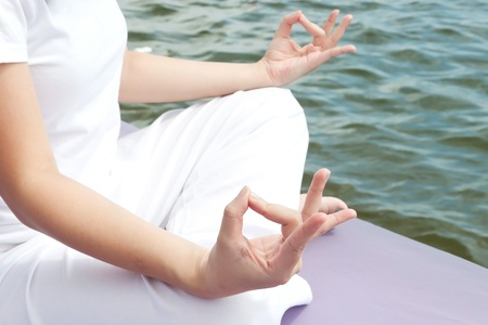 Hands of attractive young asian woman practicing yoga meditation at sunrise by the ocean photo