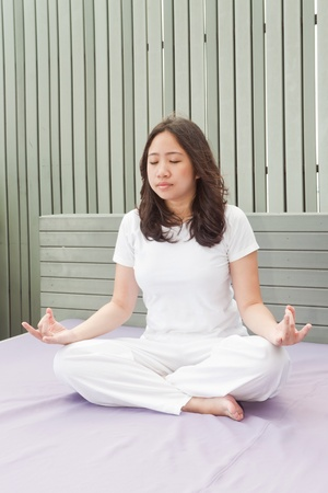 Attractive young asian woman practicing yoga meditation at sunrise