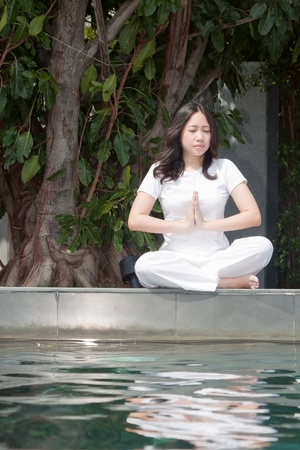 Attractive young asian woman practicing yoga meditation under the tree near the pool