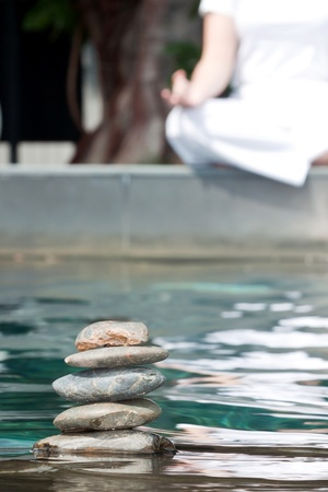 mental object: Stack of pebble stones on water with woman practicing yoga meditation in the background