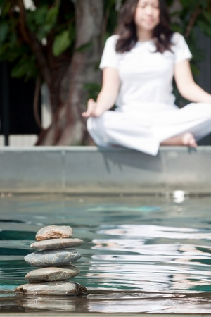 Stack of pebble stones on water with woman practicing yoga meditation in the background