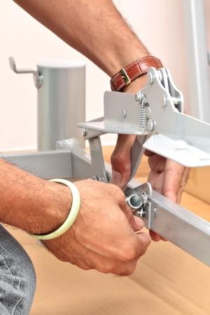 assembling: Close up of man assembling furniture  Stock Photo