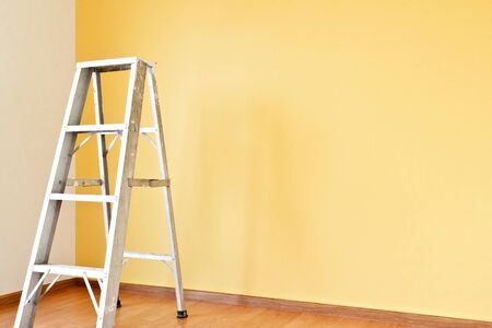 drabiny: Koncepcja domu poprawy z drabiną a ścianą żółtym Zdjęcie Seryjne