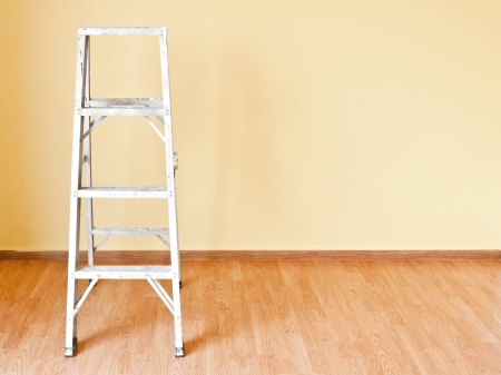 Home improvement concept with ladder and yellow wall photo
