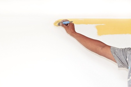 A man's hand painting a wall yellow with paint brush 版權商用圖片