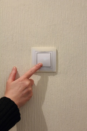 Electrical switch. Hand. Stock Photo