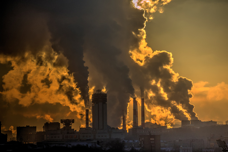 Smoky pipes of the factory in the city. Sunrise. Pollution. Stock Photo