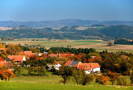 Autumn village in country surrounded by forests and fields