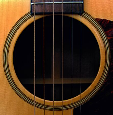 Closeup view at the sound hole of guitar with steel strings Stock Photo