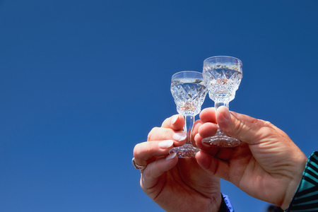 aniversary: Two hands with glasses in front of a blue sky Stock Photo