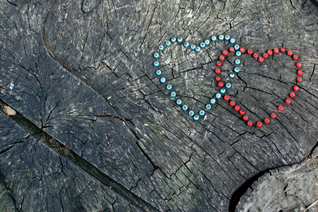 Two hearts made from blue and red beads and nailed to a wood