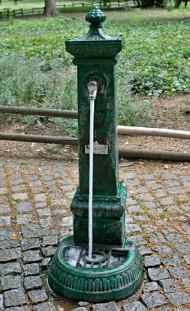 Metal water pump with flowing drinking water in the park Stock Photo