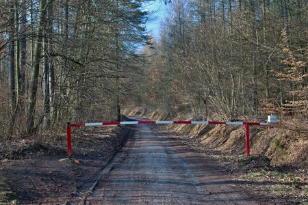Forest path closed with red white barrier