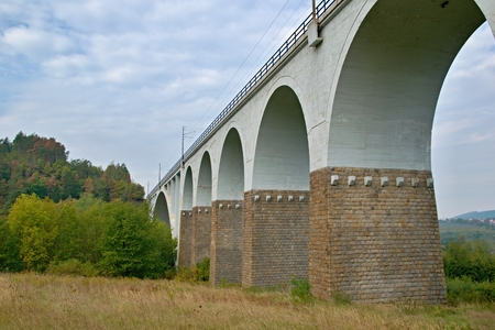 Bridge made of stones and concrete under cloudy sky