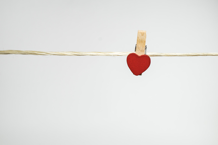 hanged woman: clothes pins with small hearts on white backgroud