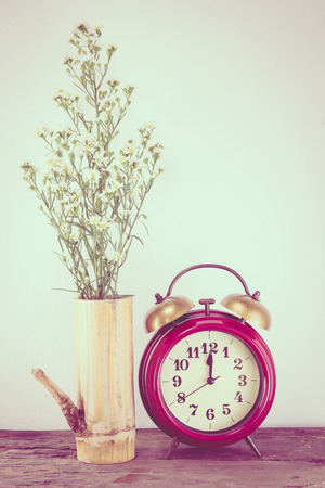 past midnight: Retro clock with flowers on the wooden floor.,vintage color tone. Stock Photo