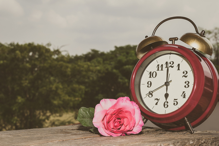 midnight hour: Retro clock with rose on the wooden floor. Stock Photo
