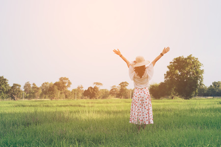 Woman breathing deep fresh air and outstretched arms  in summer field at sunrise
