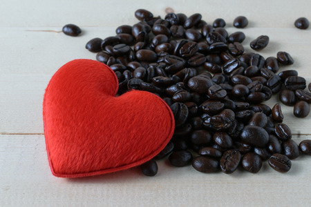Red heart and coffee beans on a wood floor.