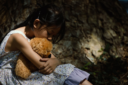 triste niña adorable con el oso de peluche en el parque, niña está abrazando a un niño de peluche bear.Upset. Foto de archivo