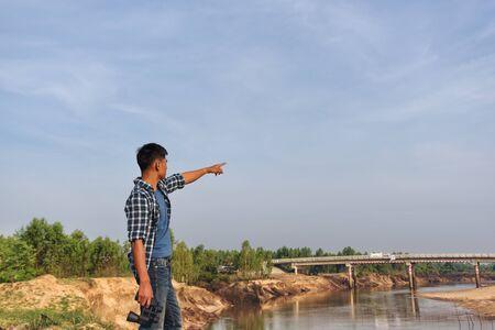 Tourist man looking through binoculars on the coast.