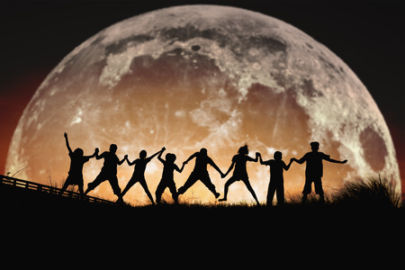 Silhouette of people jumping friendship Happiness on a  the full moon background . Elements of this image furnished by NASA. Banque d'images