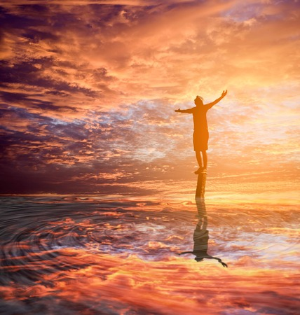 holyland:  Silhouette man with hands rise up,standing on peak open arms on the pillars with reflection on the water ,enjoying nature the sun concept world wisdom fun hope