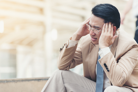 A business man with a headache from stress symptoms and severe pain. and sit down on the stairs during go to office,office syndrome concept