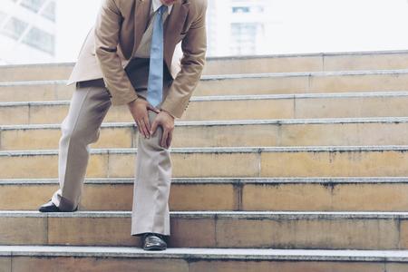 L'uomo d'affari ha il dolore e l'espressione dolorosa del ginocchio e si siede sulle scale durante il suo ingresso in ufficio Archivio Fotografico - 80916375