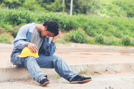 Engineer or foreman holding his head with hands ,stressed and sitting on ground with helmet   Banque d'images