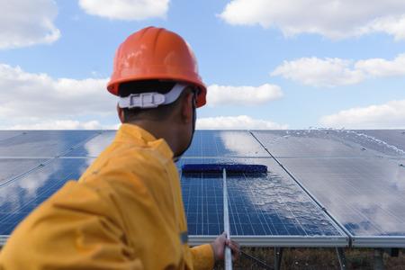 Pracownicy lub inżynierowie czyszczą czyszczenie paneli fotowoltaicznych w elektrowni słonecznej, pomysł na produkcję czystej energii, czysta energia, energia słoneczna