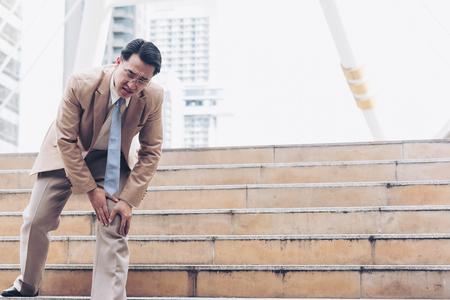 El empresario tiene el dolor y la expresión dolorosa de la rodilla y se sienta en las escaleras mientras va a la oficina Foto de archivo