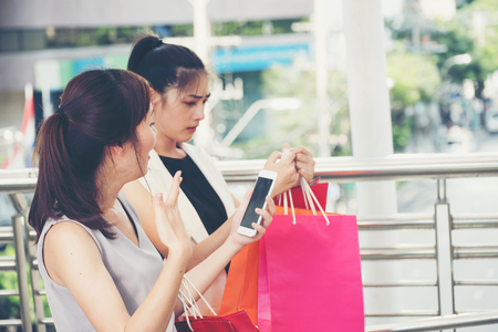 e commerce icon: Asian women are amazed during  using smart phone online shopping,online shopping,social media concept. Stock Photo