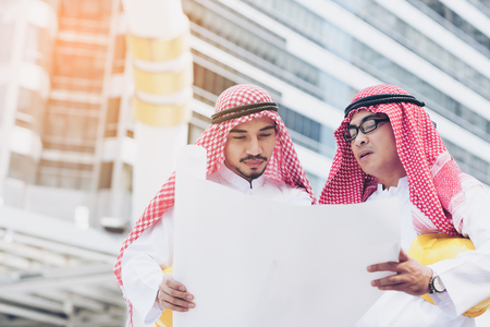 Arab businessman going over some blueprints with his engineer talking about job and verify the blueprint with commitment to success at construction site with building background